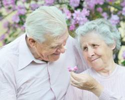 Two elder people (man and woman) are looking at each other. She is presenting a flower to him.